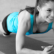 Woman doing a pilates plank with a smile on her face